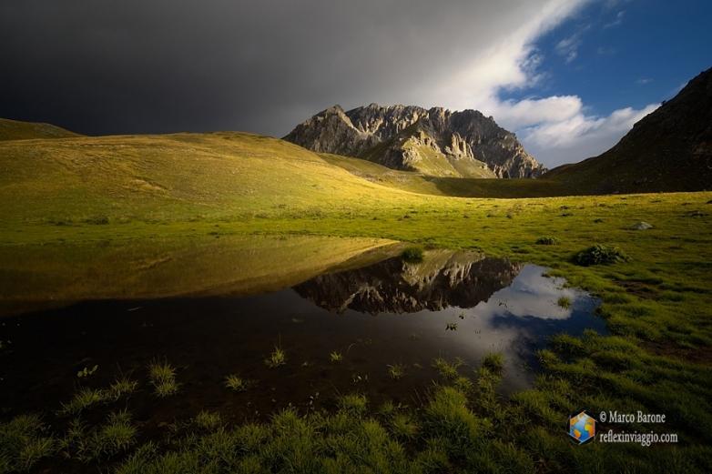 Il monte Cassorso all'alba si specchia in un piccolo laghetto.